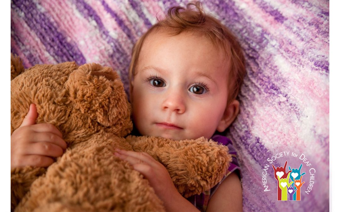 ASDC News April 2020 - photo shows a baby on a purple pillow hugging a brown teddy bear
