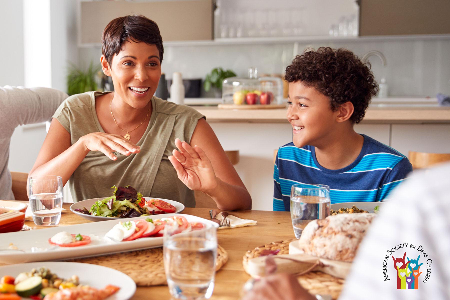 La imagen muestra a una familia sentada alrededor de una mesa conversando