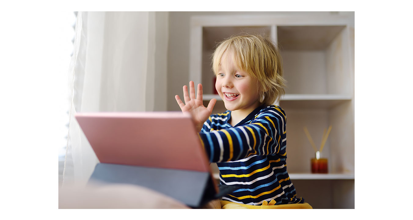 a child is waving at a computer screen
