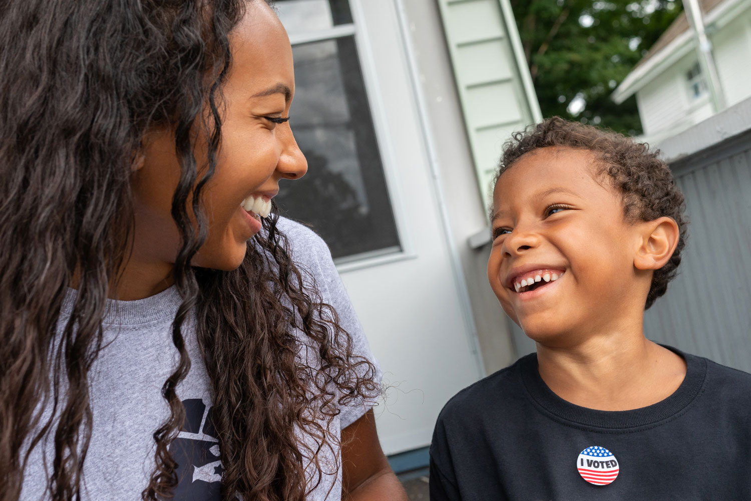 photo shows a mom and her young son looking at each other and smiling. The son is wearing an I Voted sitcker.