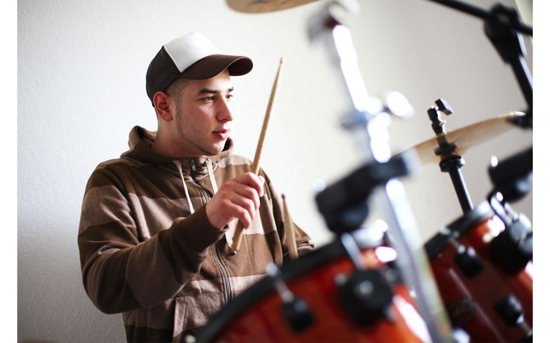 image shows teenage boy playing drums