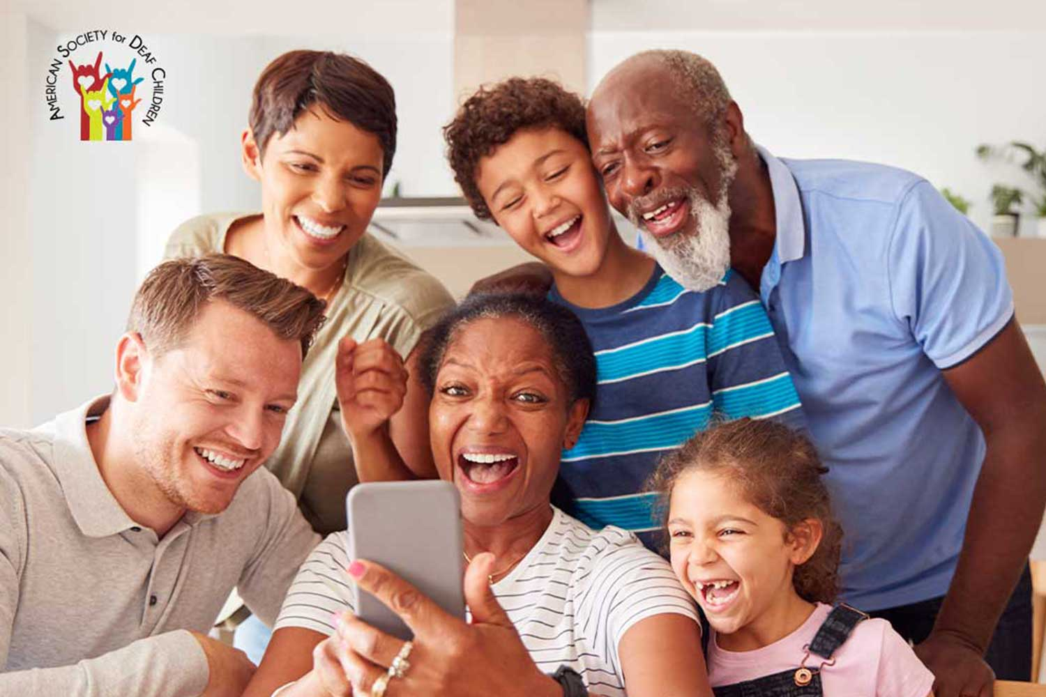 image shows a happy, multigenerational family taking a selfie or talking to someone through video chat
