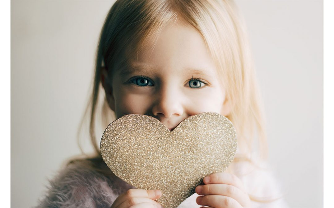 a girl holds up a glittery heart in front on her face
