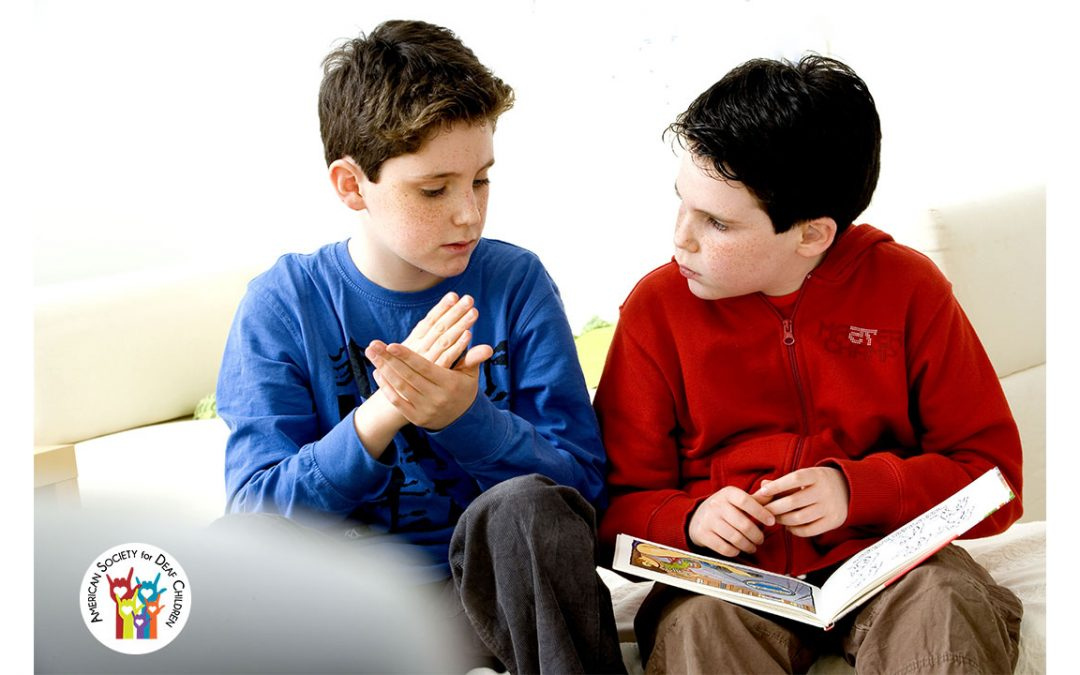 two brothers reading and signing together