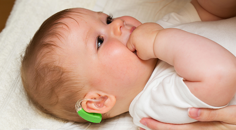a baby wearing a hearing device