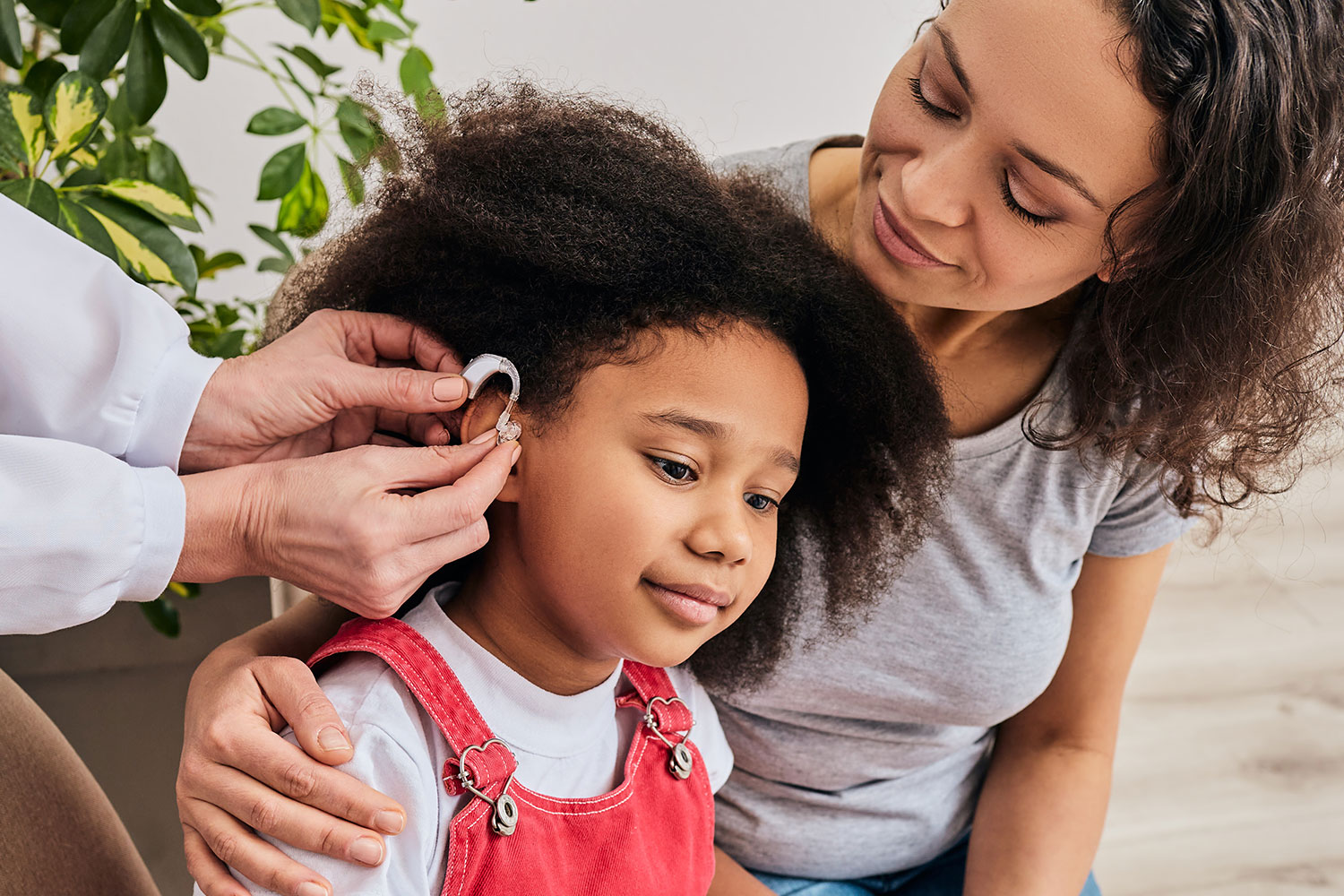 a mother looks on as her daughter is fitted with a hearing aid