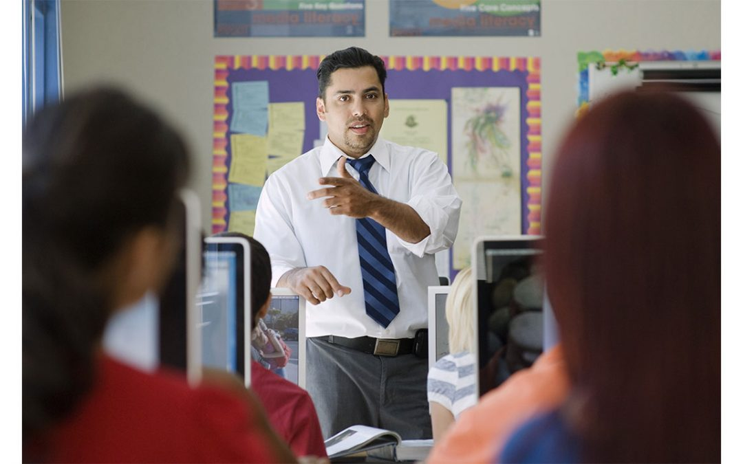 teacher in a classroom using sign language