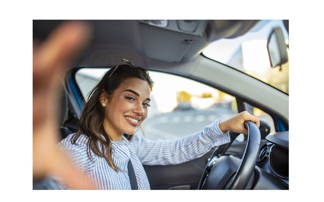 woman in driver's seat looks through the passenger window
